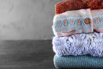Stack of warm winter clothes on grey background