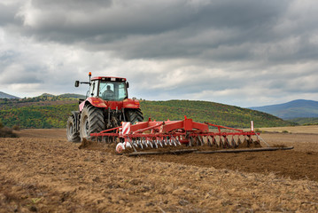 Fototapete - Farmer in tractor preparing land with seedbed cultivator