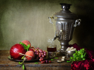 Still life with fruits placed with hot cup of tea, silver samovar, brown sugar, fresh mint and red silky scarf on rustic wooden table .