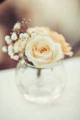 Single flower of white rose in round glass vase on the table. Floral decor elements. Concept for romantic greeting card  birthday, valentine, mothers day or weeding