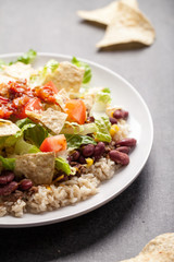 Taco Salad stacked on a bed of brown rice angled view
