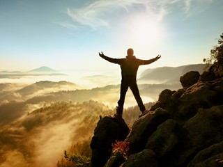 Sunny fall morning. Happy hiker with raised hands in air stand on rock Wall mural