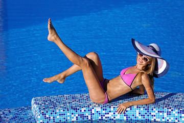 Beautiful young woman sitting on ledge of swimming pool