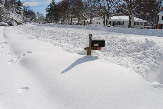 Snowed in mailbox surrounded by snow after the plow goes by
