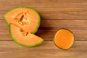 Cantaloupe melon fruit and glass of juice on wooden background. Top view.