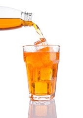 Pouring orange energy soda drink in glass with ice