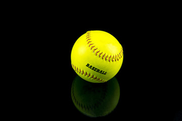 Baseball yellow on a black background .