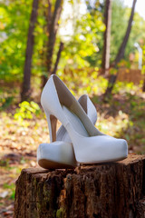 The beautiful shoes of the bride with flowers on the side.