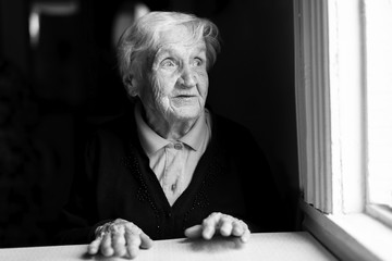 An elderly woman stares out of the window. Black and white photo.