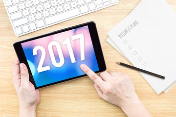 Hand touch tablet with 2017 year number on screen with business
