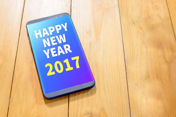 Happy new year 2017 year on mobile screen on wood table,Digital