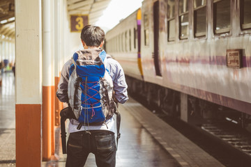 Traveler with backpack in train station.