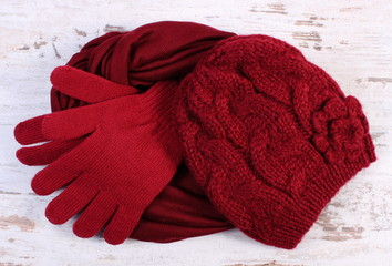 Pair of woolen gloves, cap and shawl for woman on old wooden background