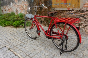 Vintage Red bicycle near the window of old brick wall home background