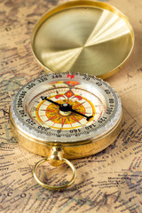 the old gold compass with cover on vintage map, macro background