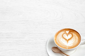 A cup of coffee latte with spoon on wood blackground