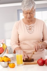 Elderly lady slicing healthy bread