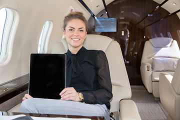 woman in corporate jet showing tablet computer