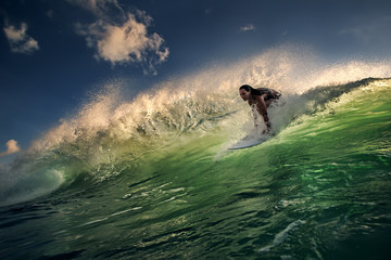 A surfer girl riding inside an ocean green wave lit with sunset light. Watersport Activity in Indonesian island Bali. Green water with blue dark sky.