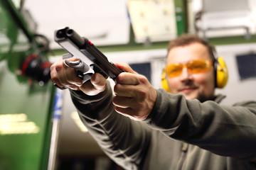Strzelnica sportowa. Mężczyzna na strzelnicy przeładowuje pistolet