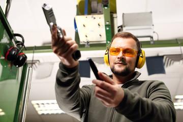 Pistolet. Mężczyzna na strzelnicy przeładowuje pistolet