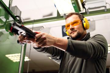 Nauka posługiwania się bronią palną. Mężczyzna na strzelnicy przeładowuje pistolet