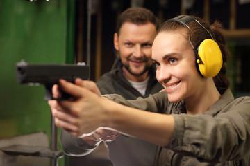Relaks na strzelnicy, kobieta strzela z glocka. Kobieta bierze lekcje strzelania z broni krótkiej na strzelnicy sportowej