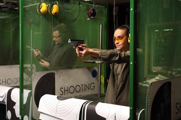 Kobieta na strzelnicy. Kobieta celuje do tarczy z pistoletu