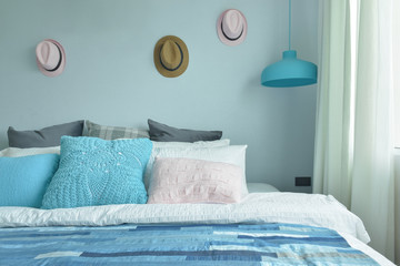 Light blue, pink and gray pillows on bed with blue tone bedroom
