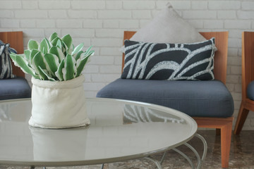 Decorative plant pot on center table with easy chair in background