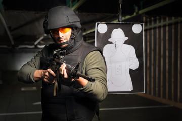Żołnierz strzela z karabinu na strzelnicy. Mężczyzna  w kamizelce kuloodpornej strzela na strzelnicy z karabinu