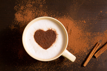 Cup of coffee with heart pattern of cinnamon