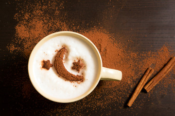 Cup of coffee with moon and stars pattern of cinnamon