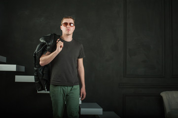 studio photography young brutal guy. man in sunglasses, T-shirt, jeans keeps black leather jacket, slung over his shoulder. black background painted walls and white stairs