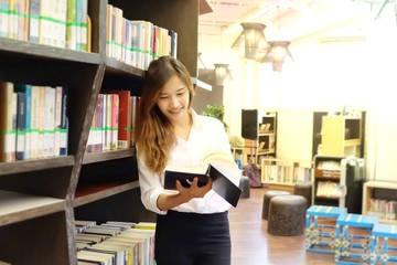 Beautiful woman  in a university library. Student with open book reading it in college library