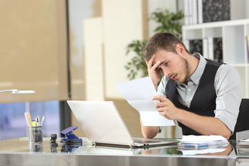 Sad businessman reading a letter at office