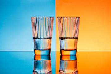 Two glasses with water over blue and orange background.