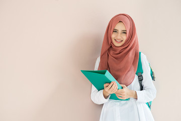 Beautiful muslim student girl standing and holding document.