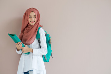 Beautiful islam student girl standing and holding document.