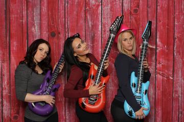 Drei junge Frauen spielen auf Platikgitarren - Photobooth Party vor rotem Hintergrund