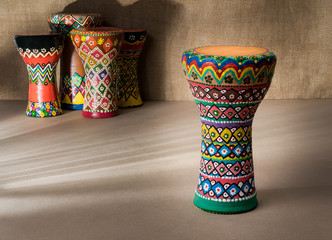 Front view of decorated colorful pottery goblet drum on background of goblet drums, wooden table with vanishing shadow lines, and sackcloth wall. Low light studio shot