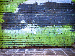 green brick wall getting older from the bottom