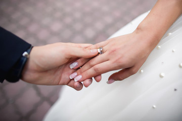 Wedding rings, proposal of marriage. Groom holding bride hand with wedding and proposal rings