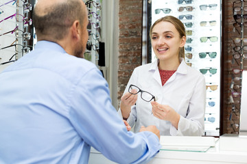 Friendly female ophthalmologist and mature patient