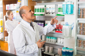Pharmacist and pharmacy assistant helping