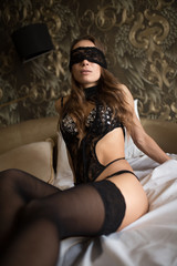 Sexy brunette woman in black lingerie sitting on a bed with blindfold