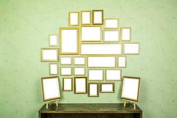 Many empty golden wooden frames with copy space on green wallpapered wall and bookshelf.