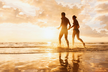 Happy cheerful couple running to the sea, water splashes, sunset