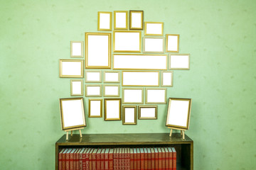 Many empty golden wooden frames with copy space on green wallpapered wall. Bookshelf with red books.