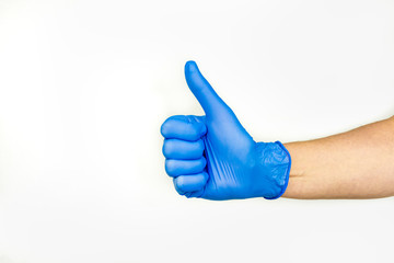 Thumbs up. Profile view of hand in blue medical glove. Inside of hand.